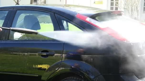 Muž mytí vozu Ford Focus se silným proudem vody na čerstvém vzduchu