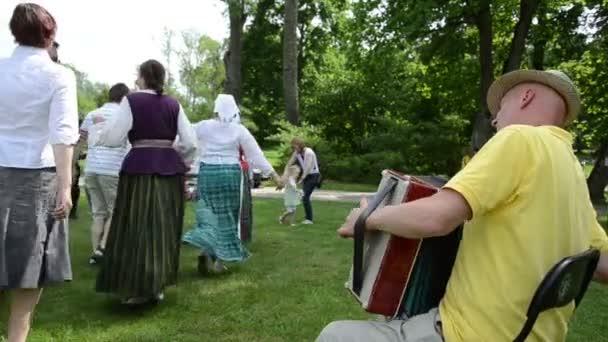 Mužské hudebník si hrát akordeon a lidé tanec ve dvojicích