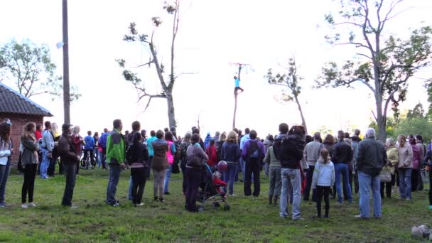 People watch boy high in tree trying reach prize hang on branch