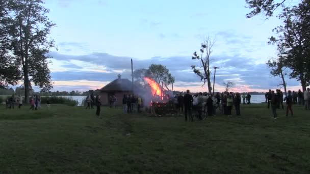 Landscape of burning campfire near lake and crowd of people