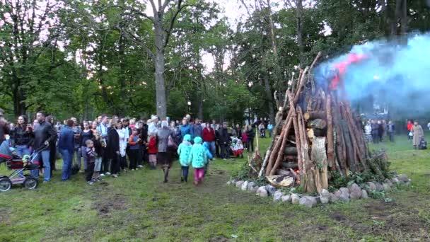 People flock around large beautifully build burning fire