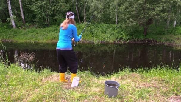 Těhotná žena v žluté boty chytat ryby. kočka sedí blízko kbelík
