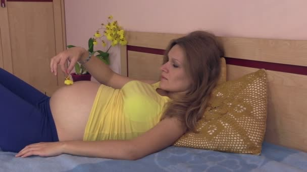 Pregnant woman caress stomach with yellow orchid flower petal