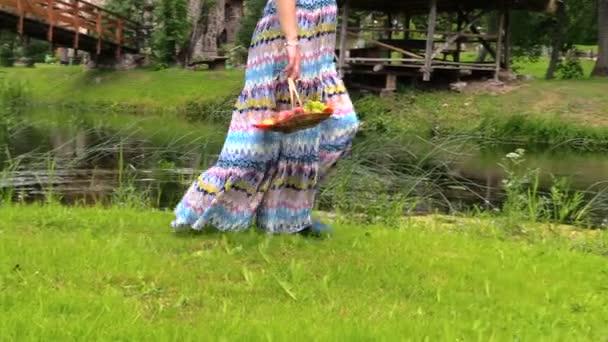 Terhes nő ruhában járni-folyó partján, a gyümölcs-kosár