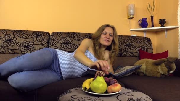 Simogatása terhes asszony hasát enni a szőlő és a kapcsoló Tv csatorna