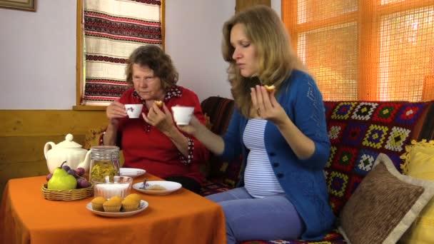 Starší babička a těhotnou dívku jíst sladkosti, čaje