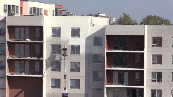 Dělník na speciální výtah malování stěn nový bytový dům