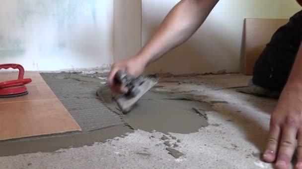 Tiler worker hand spread adhesive material. Left side sliding