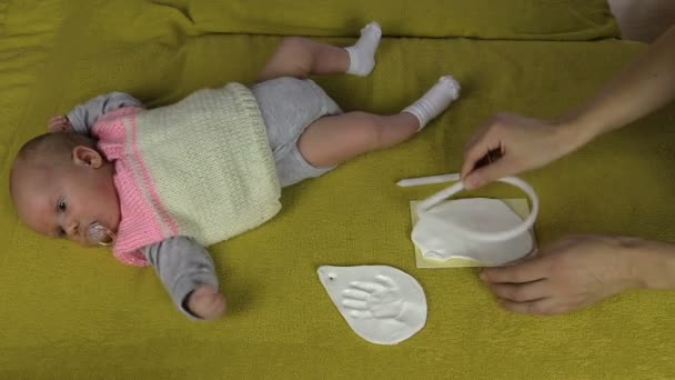 Mother create infant baby footprint on special material