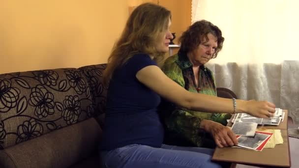 Pregnant granddaughter woman with senior grandmother watch photo