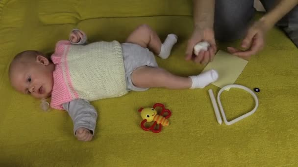 Newborn baby lie on sofa and mother hands mix special material