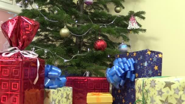 Barevné dárkové krabičce s mašlí pod roztomilý vánoční stromeček