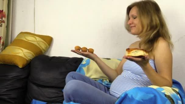 Hladoví těhotná žena učinit rozhodnutí, co jíst. Drdol nebo dorty