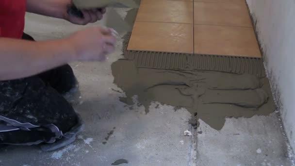 Položit keramická dlažba - muž šíří materiálu. Closeup