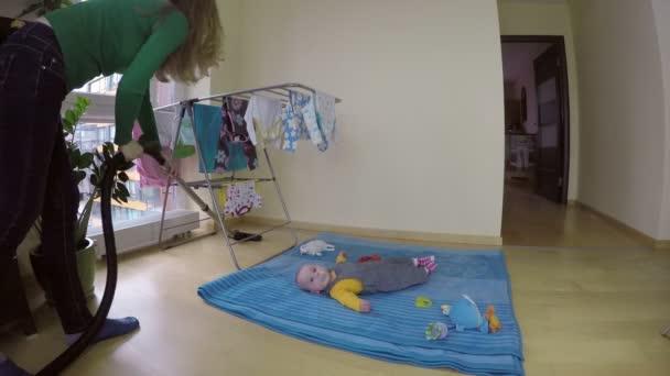 Kindermädchen kümmern sich um die kleine Tochter und reinigen das Haus mit Staubsauger. 4k