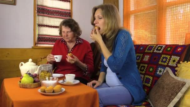 tazze di porcellana di donna incinta visita nonna bere tè, mangiare la torta
