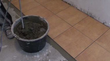 Operaio mescolare il cemento colla per piastrelle sul secchio con