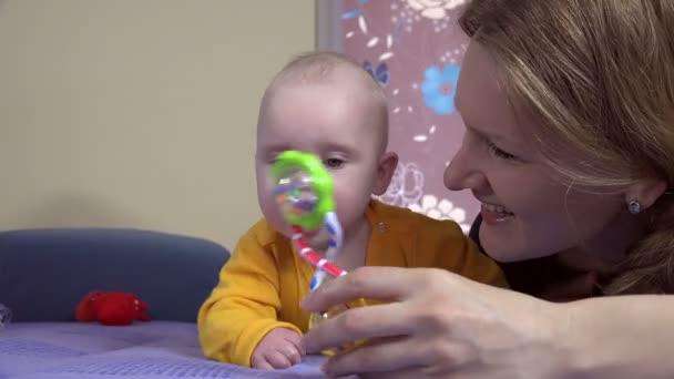 šťastná maminka vyzkoušet, přitahují pozornost dítěte s chrastítkem box hračka. 4k