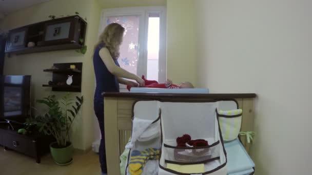 Anya levetkőzik neki baba szervezet ruhát pelenka pelenkázó. 4k