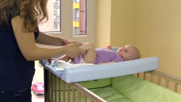 mother make therapeutic foot massage for baby on swaddle board