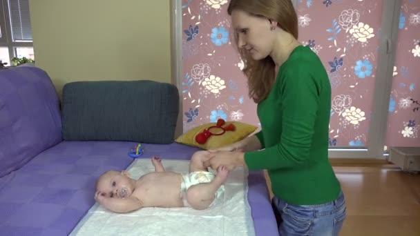 Matka masáže a cvičení malé dítě dcera nohy na postel. 4k