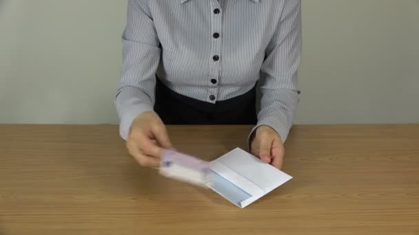 žena ruku dal 500 euro bankovek na bílé obálky