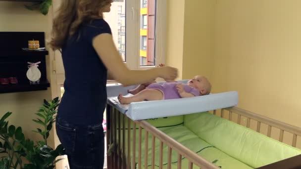 Baby masáž. Maminka, aby dítě břicho. Dítě leží na desce zavinout dítě