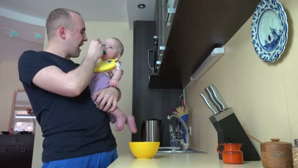 father talk with baby daughter and feed with mash in spoon. 4K