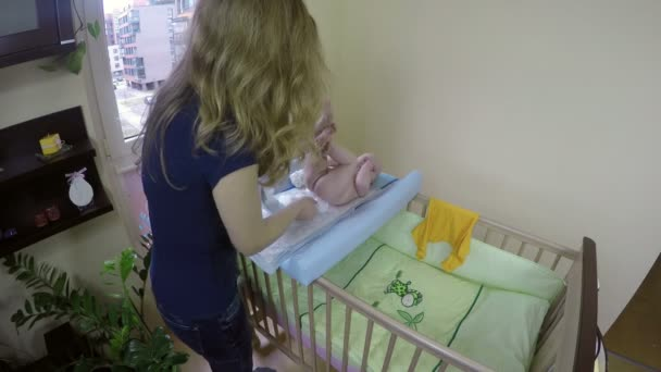 Mother woman changing her baby diapers on her bed. 4K