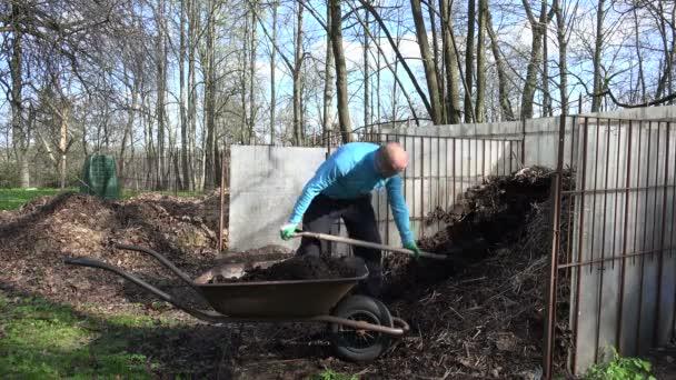 Фермер людина з Вила копати компост гумусу до кургану. 4 к– стокове відео 2e8214f706046
