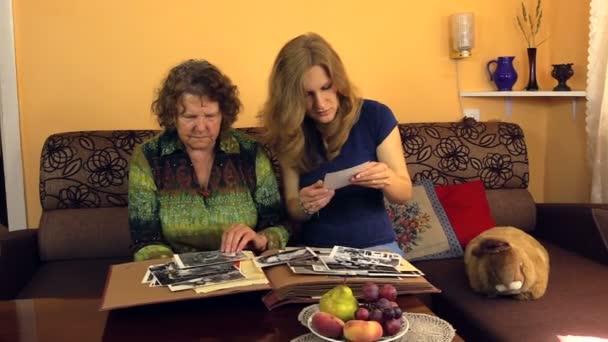 Šťastný starší žena s vnučkou hodinky fotografiemi v staré album