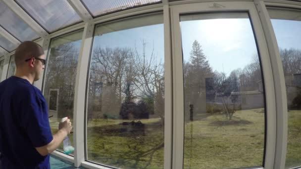 muž pracovník mytí oken s postřikem a čisticí houba. 4k