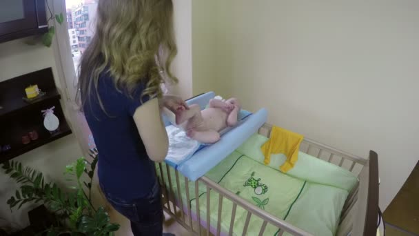 Mother woman change her baby diapers on changing table. 4K