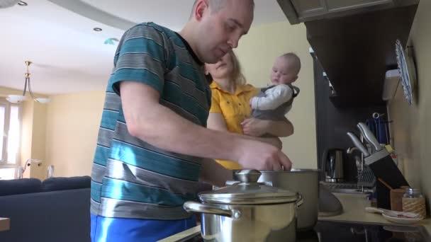 rodina s dítětem připravit večeři v kuchyni. maminka chuť polévková lžíce