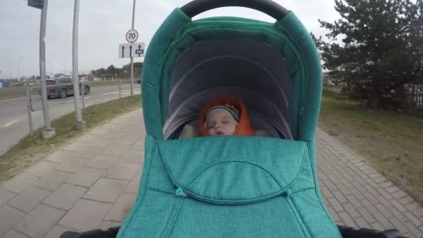 9338c4db7 little kid with romper sleep buggy ride across city street. 4K ...