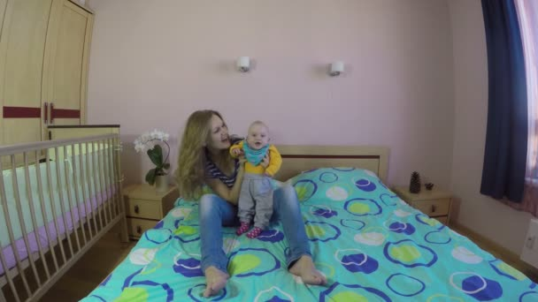 Mother and 5 month old daughter baby laugh and play on bed. 4K