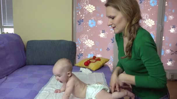 Masseuse massaging little baby back on couch. baby care.