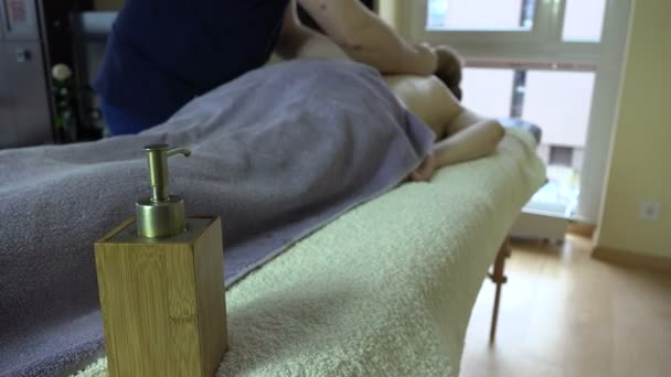 Massage oil and hand touch woman back covered with towel. 4K
