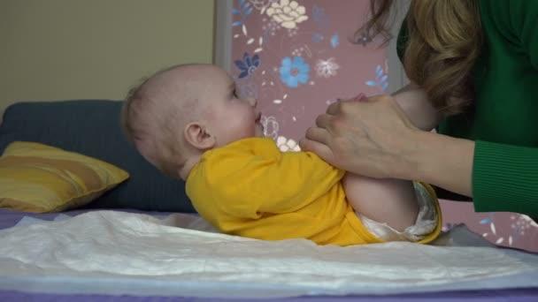 anya, hogy gyakorolja az 5 hónapos kislány a kanapén. Babaápolás.