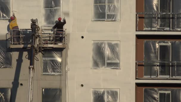 Worker men paint house wall with sprayer tool and roller. 4K
