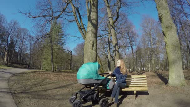 Happy mother with baby in buggy sit on bench in spring park. 4K
