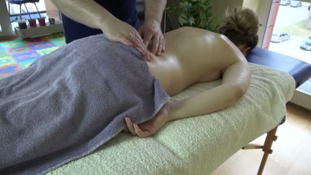 Massage Therapeuten behandeln weiblich Client auf Tisch in der Wohnung. 4k