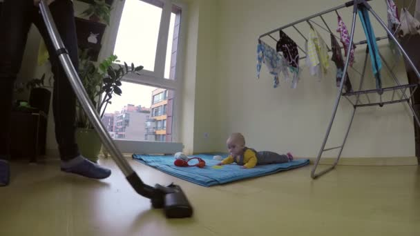 housewife cleaning floor with cleaner and baby on carpet mat. 4K