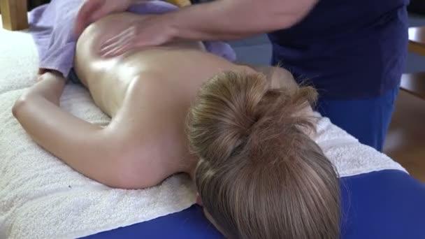 rubber man hands massage female client woman back. 4K