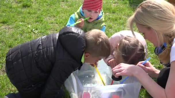 Jungen und Mädchen mit Stroh spielen Entenrennen im kleinen Wasserbecken. 4k