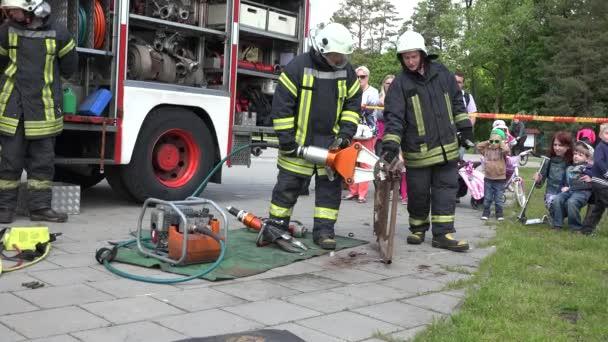 Hasič záchranář ukazují zařízení poblíž hasič náklaďák. 4k