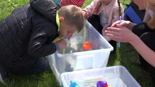 Kinder mit Stroh spielen Entenrennen im kleinen Wasserbecken. 4k