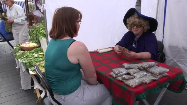 fortune-teller witch woman predict future for clients in outdoor event. 4K