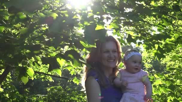 mladý radostné matka s dcerou chodit mezi tulipánovník větví. 4k