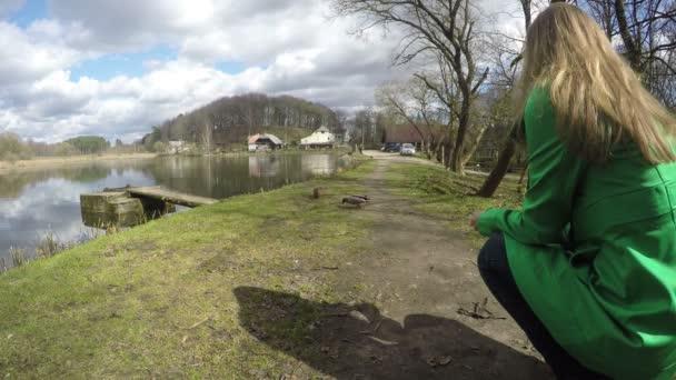 dívka, krmit chléb crumb kachna na břehu jezera. Pohled od zad. 4k